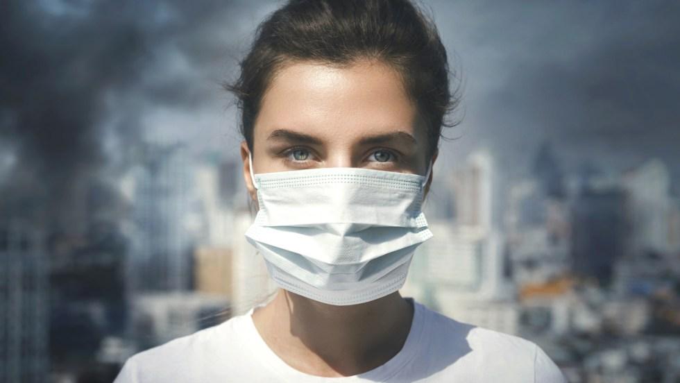Une jeune femme portant un masque devant un environnement urbain marqué par le smog, la pollution et les gaz à effet de serre