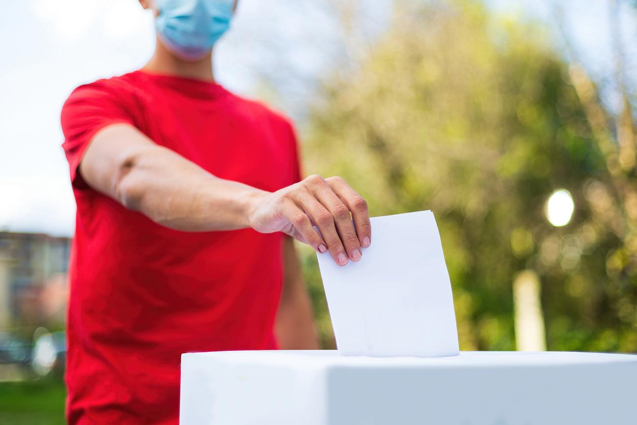 Un homme en chandail rouge portant un masque chirurgical dépose son bulletin de vote dans une boîte de scrutin, à l'extérieur devant un paysage naturel.