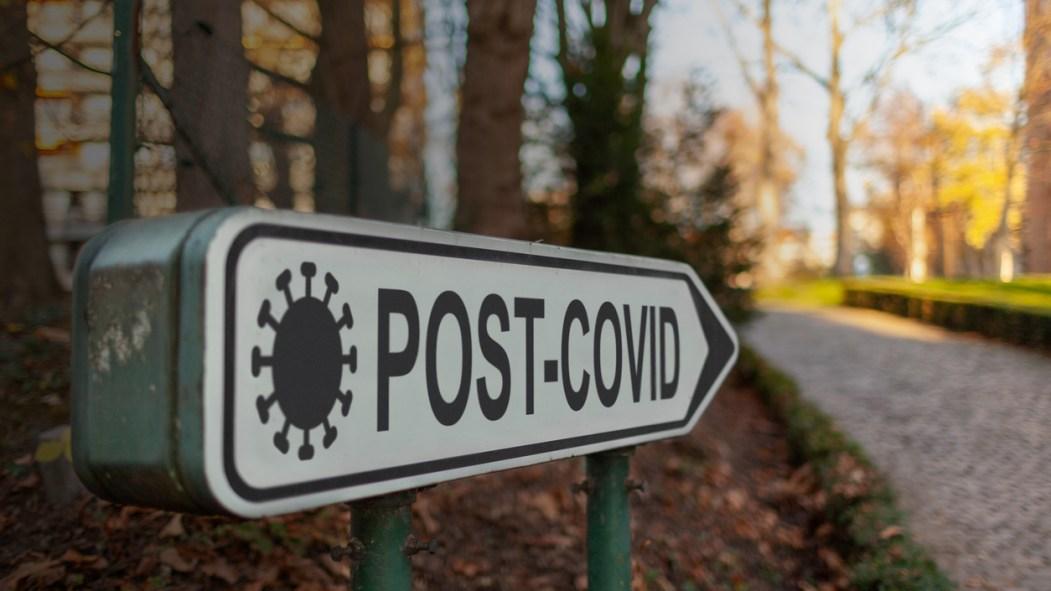 Une pancarte affiche les mots «post-covid» devant un environnement naturel