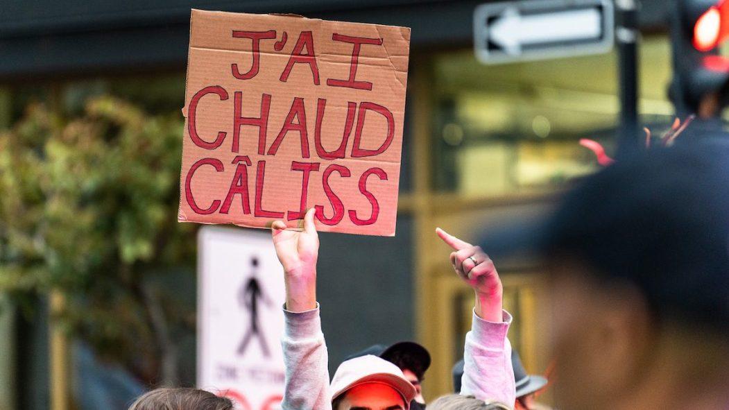 Un manifestant écologiste tient une pancarte qui dit «J'ai chaud câliss» pendant une manifestation pour l'environnement avant le débat des chefs à TVA.