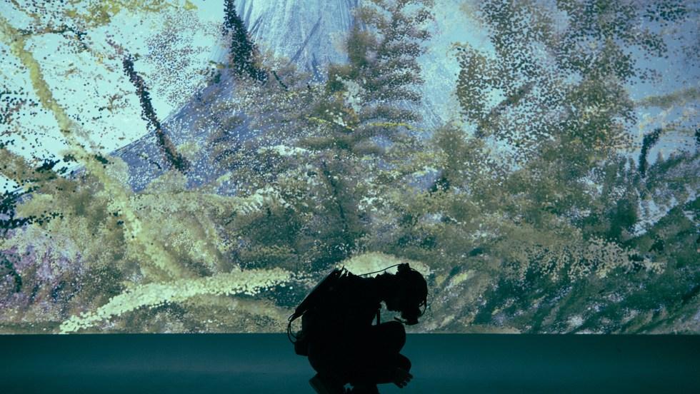 Un homme en scaphandrier est accroupit devant un énorme aquarium dans l'exposition «We Live in an Ocean of Air» de Marshmallow Laser Feast.