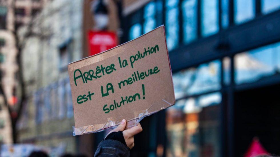 Une main tient une affiche disant «arrêter la pollution est la meilleure solution» lors d'une manifestation pour la lutte aux changements climatiques tenue à Montréal