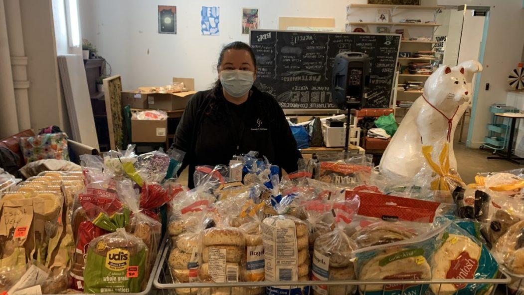Atlantide Desrochers devant l'étalage de pains et viennoiseries prêts à être distribués