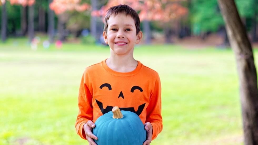Un jeune garçon tient une citrouille turquoise.