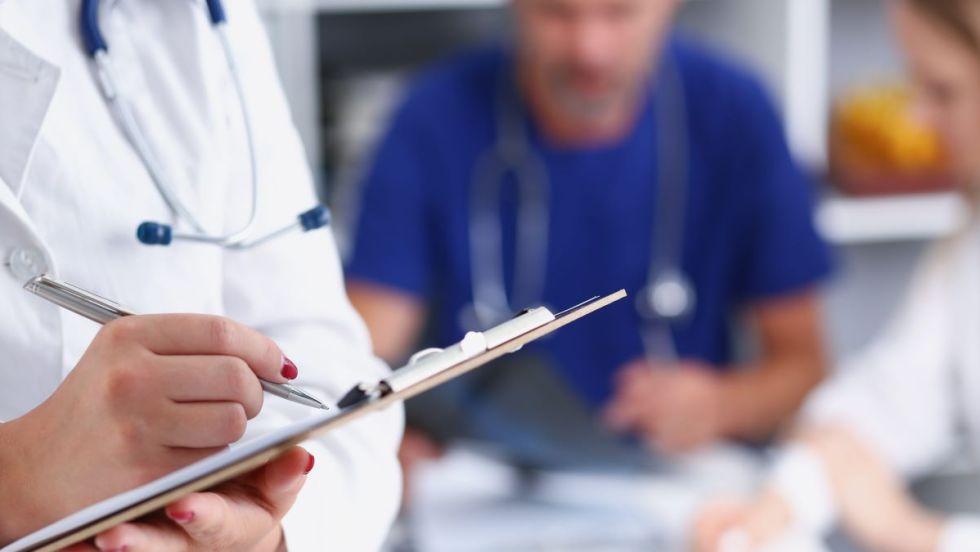 Une médecin de famille écrit dans un calepin alors qu'un collègue masculin est assis en arrière-plan.